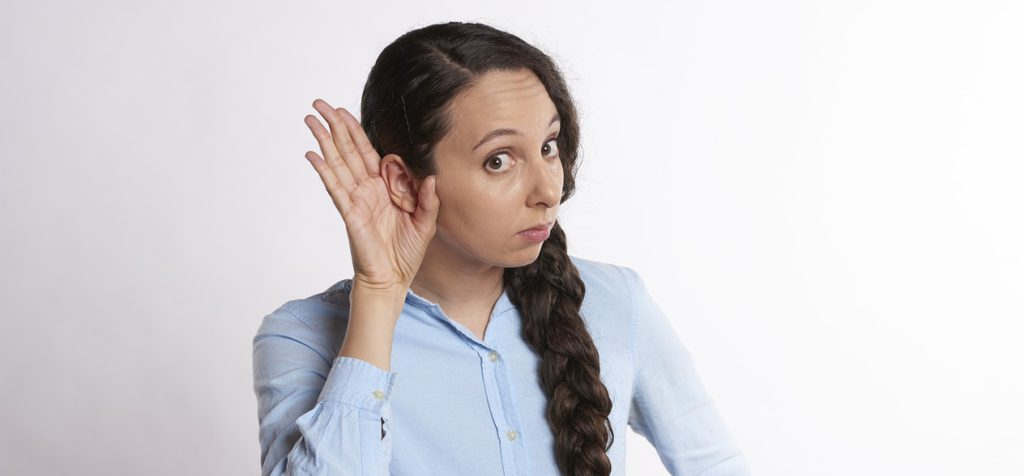 Woman in blue shirt and with long braid cups hand to ear in listening pose