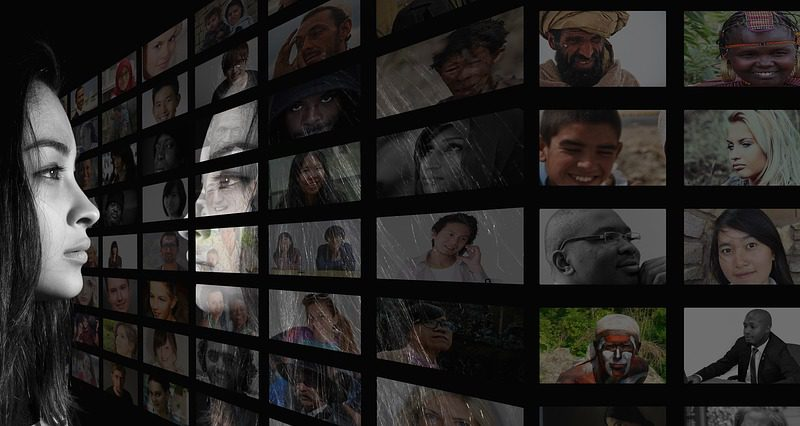 Woman looks at images of many faces on a screen