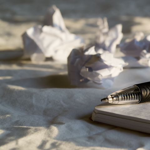 Ballpoint pen on edge of journal with crumpled paper in background, representing a writer who is blocked